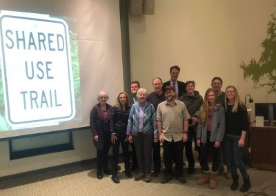 Public meeting with Shared Use Trail sign in background